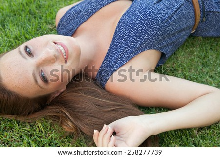 Beauty portrait of an attractive joyful young beautiful tourist woman laying down on green grass in a park, relaxing on a summer holiday, smiling. Healthy living and well being lifestyle, exterior. - stock photo