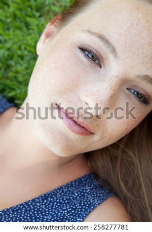 Beauty portrait of an attractive joyful young beautiful tourist woman laying down on green grass in a park, relaxing on a summer holiday, smiling. Healthy living, beauty lifestyle, exterior. - stock photo