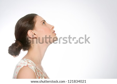 Beauty portrait of an attractive young woman profile, looking up with a glow around her.