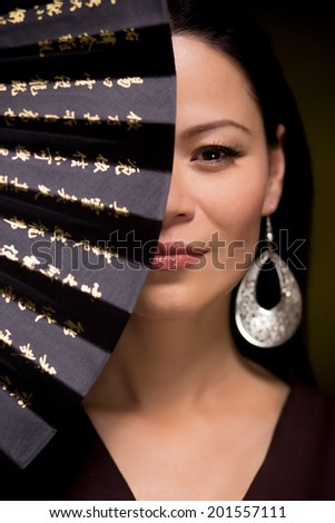 Beauty portrait of asian woman with hand fan on dark background - stock photo