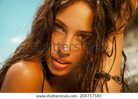 beauty portrait of attractive brunette with golden tan and wet hair. Toned in warm colors. horizontal shot by the sea. - stock photo