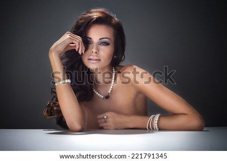 Beauty portrait of attractive brunette woman with elegant makeup, wearing pearls jewelry. Girl looking at camera. - stock photo