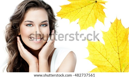 beauty portrait of attractive caucasian smiling young woman brunette isolated on white studio shot  toothy smile face looking at camera hands yellow marple autumn leaves