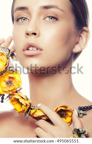Beauty portrait of attractive caucasian young girl with natural make-up and yellow flowers necklace looking at camera. Studio shot Isolated on white background. Toned