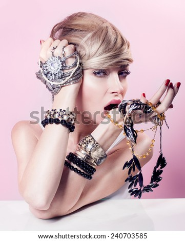 Beauty portrait of attractive delicate blonde woman with jewelry on hands. Girl looking at camera. Pink background. - stock photo