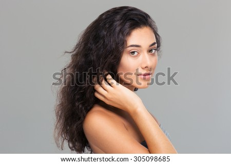 Beauty portrait of attractive girl looking at camera over gray background