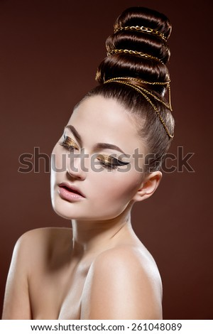 Beauty portrait of attractive model face with bright visage. Gold eye makeup and soft beige lips make-up. Gold arrow make up. Creative hairstyle - stock photo