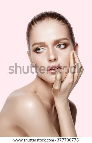 Beauty portrait of attractive model with professional makeup. Blue eyes, brunette hair. Fresh, clean skin. Tender colors Gold hands. Pink background not isolated. - stock photo