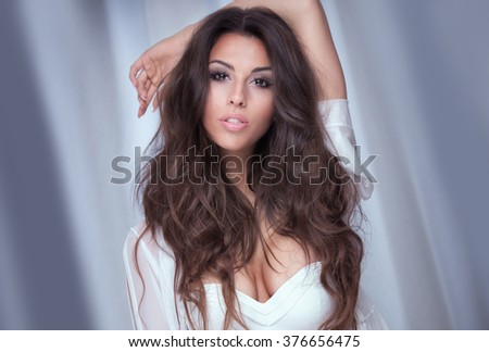 Beauty portrait of attractive young woman with brown long hair. Girl looking at camera. Glamour makeup. - stock photo