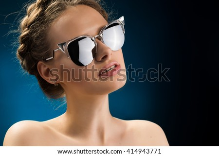 Beauty portrait of beautiful blond woman with stylish hairstyle in sunglasses. Professional makeup. Young beautiful lady with neutral big lips and naked shoulders. Gorgeous fashion beauty close up.