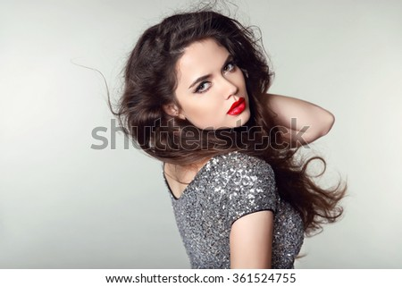 Beauty Portrait of beautiful brunette woman with red lips and curly hair style in party dress isolated on studio background. Makeup. - stock photo