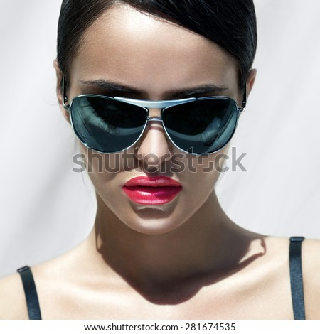 Beauty portrait of beautiful brunette woman with stylish hairstyle in sunglasses. Professional makeup. - stock photo