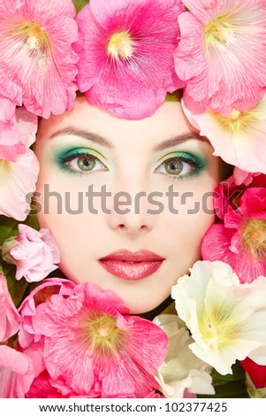 beauty portrait of beautiful female face with pink, red and white mallow flowers frame - stock photo