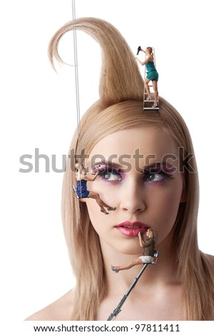 beauty portrait of blond young girl with make up and hair style under costruction with little woman working around the face