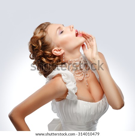 Beauty Portrait of bride wearing in wedding dress with necklace, studio photo - stock photo