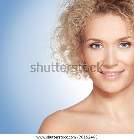 Beauty / Portrait of caucasian mid adult woman with beautiful blue eyes on a blue background - stock photo