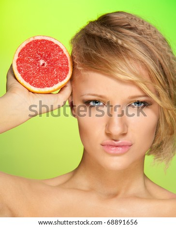 Beauty portrait of confident young attractive woman with grapefruit