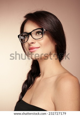 Beauty portrait of elegant charming woman wearing eyeglasses posing in studio. Young lovely Caucasian female with glamorous hairdo and makeup.  - stock photo