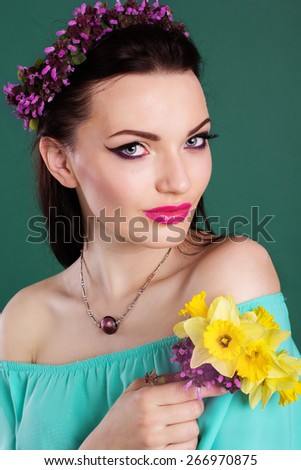 Beauty portrait of pretty girl with purple wreath of flowers in hair and fashion makeup is holding daffodil flowers in hands - stock photo