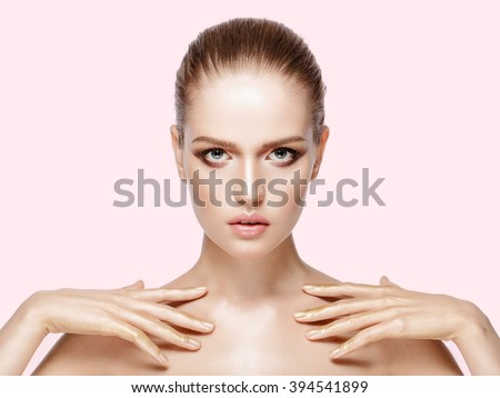 Beauty portrait of pretty model with professional makeup. Brunette hair. Fresh, clean skin. Bright colors. Gold hands. Pink background, not isolated. - stock photo