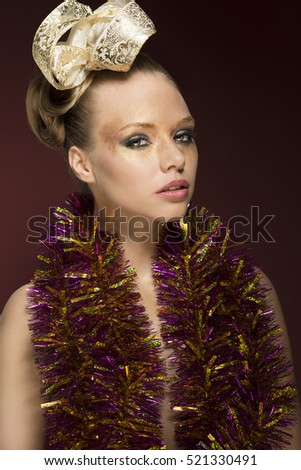 beauty portrait of pretty woman with creative glossy golden make-up, ribbon in the hairdo and tinsel on her naked breast