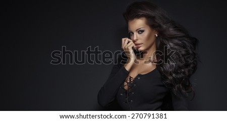 Beauty portrait of sensual attractive woman with long curly black hair and perfect makeup. Girl looking at camera. - stock photo