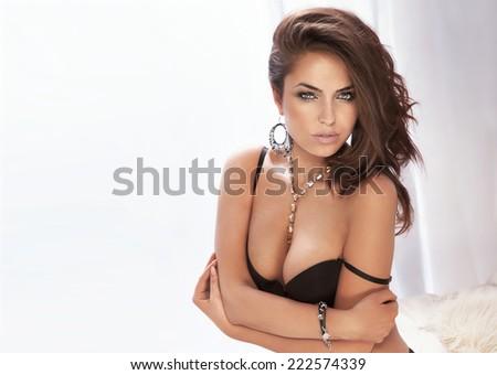 Beauty portrait of sensual brunette woman posing in elegant lingerie, looking at camera. - stock photo