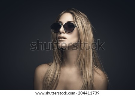 Beauty portrait of sexy blonde woman with sunglasses against grey background