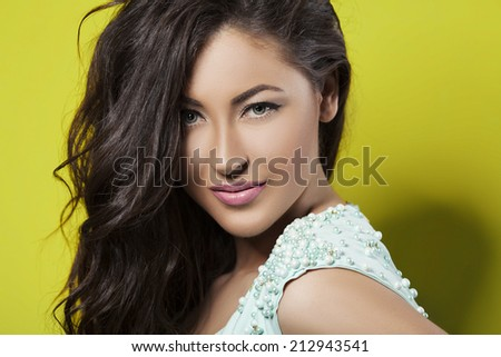 Beauty portrait of sexy curly hair brunette woman over yellow background - stock photo