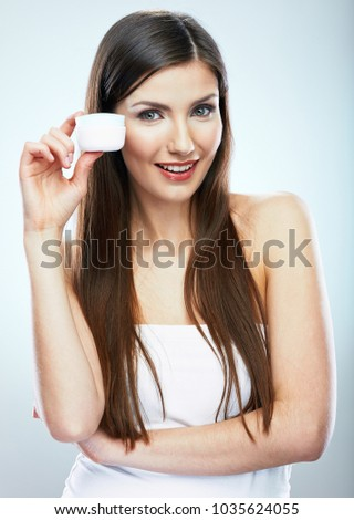 Beauty portrait of smiling girl holding skin cream. Isolated studio portrait.