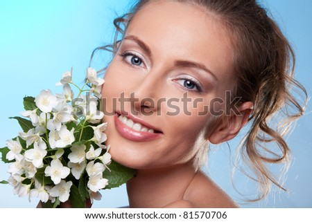 Beauty portrait of smiling woman holding bouquet of white spring jasmine flowers on blue with curly hair - stock photo