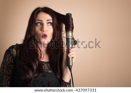 Beauty portrait of woman curling her hair, plenty of copy space - stock photo