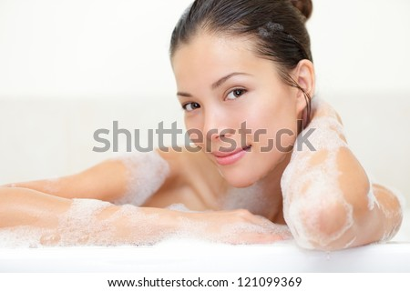Beauty portrait of woman in bathtub with bath foam smiling happy looking serene at camera. Beautiful young mixed race Caucasian / Asian woman. - stock photo
