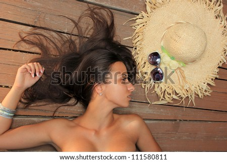 Beauty portrait of woman on the beach wearing straw hat - stock photo