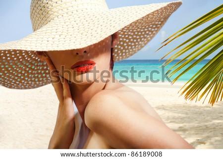 Beauty portrait of woman on the beach wearing straw hat - stock photo