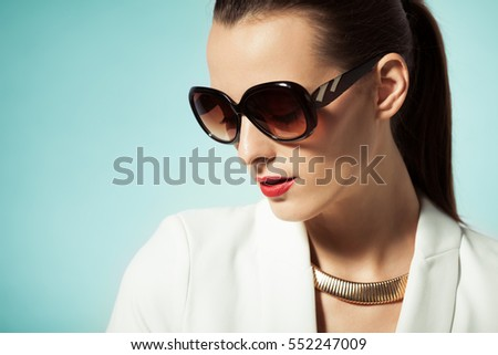 Beauty portrait of woman wearing sunglasses and necklace.