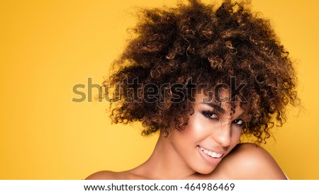 Beauty portrait of young african american girl with afro hairstyle. Girl posing on yellow background, looking at camera, smiling. Studio shot.
