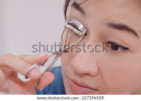 Beauty portrait of young asia woman using eyelash curler - stock photo