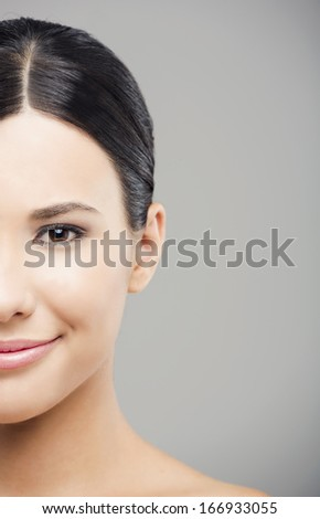 Beauty portrait of young asian woman smiling, over a gray background. - stock photo