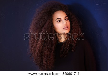 Beauty portrait of young attractive african american girl with brown eyes. Long curly hair. Girl looking at camera. - stock photo