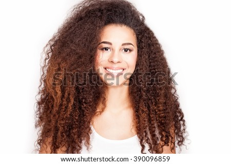 Beauty portrait of young attractive african american girl with toothy smile. Long curly hair. Girl looking at camera. White background. - stock photo