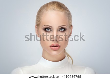 Beauty portrait of young attractive blonde woman with natural makeup. Beautiful female face. Closeup photo. Fashion model with blue eyes looking at camera.