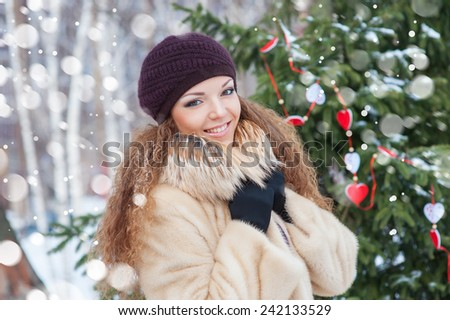 Beauty portrait of young attractive woman over snowy Christmas background. - stock photo