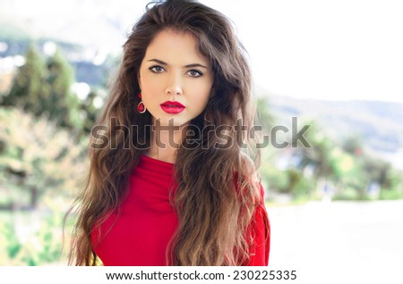 Beauty portrait of young attractive woman with red lips and long healthy wavy hair, outdoor photo. - stock photo