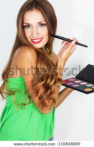beauty portrait of young beautiful woman with makeup brush and palette of eye shadows isolated on white background