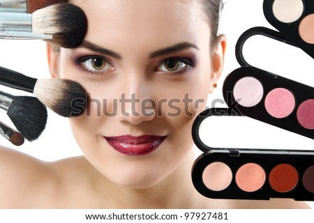 beauty portrait of young beautiful woman with makeup brushes and palette of eye shadows isolated on white background - stock photo