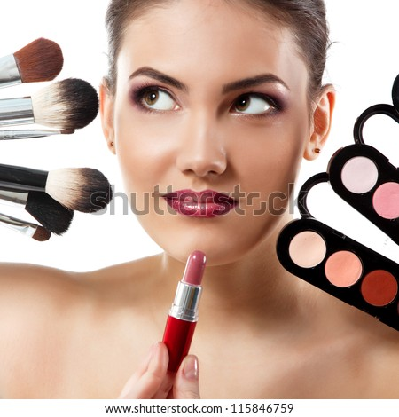 beauty portrait of young beautiful woman with makeup brushes, lipstick and palette of eye shadows isolated on white background - stock photo