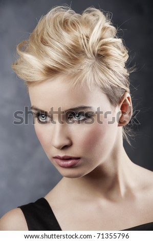 beauty portrait of young blond girl with fashion hair style and make up on dark background