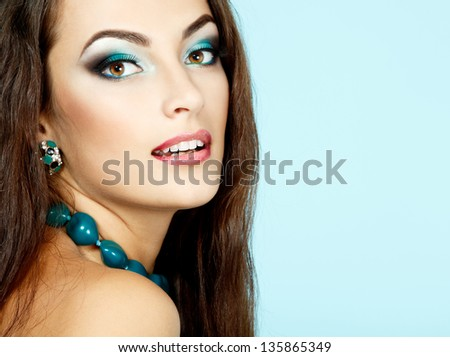 Beauty portrait of young fresh woman with long brown healthy hair and beautiful makeup. Isolated on blue background - stock photo