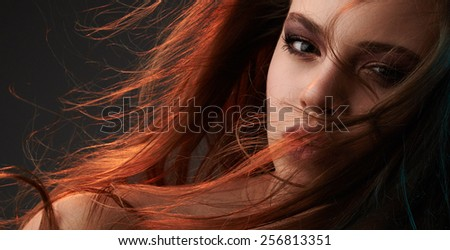 Beauty portrait of young girl with long hair on grey background